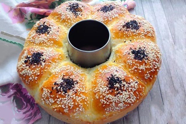Потрясающе вкусный пирог из доступных продуктов. Тесто мягкое, воздушное, почти невесомое, прекрасное в работе. Начинка — картофельное пюре с зеленью и сливочным маслом. Пирог настолько легко, просто и быстро готовить, что с ним справится любая хозяйка.  Ингредиенты:  Для теста  Молоко (теплое) — 110 мл Йогурт (кефир, пахта) — 110 мл Белок яичный — 1 шт Масло сливочное — 30 г Сахар — 2 ч. л. Соль — 1 ч. л. Дрожжи (мгновенные) — 10 г Мука пшеничная (1 стакан = 200 мл) — 3…3.5 стак. Масло растительное — 25 мл Для начинки  Картофель — 420…450 г Масло сливочное (ТМ Экомилк) — 4…5 ст. л. Зелень — 1 пуч. Соль — по вкусу Перец черный — по вкусу Для смазки  Желток яичный — 1 шт Вода — 1 ч. л. Кунжут — 1…2 ст. л. Семена (чернушка) — 1 ст. л.  В миску налить теплое молоко, добавить дрожжи и дать постоять 5-10 минут. Затем добавить яичный белок, соль, йогурт, растопленное сливочное масло и хорошо перемешать венчиком. Понемногу добавить муку и замесить мягкое тесто. Сразу всю муку добавлять не нужно. Для начала всыпать 2,5 стакана, перемешать и затем добавлять по 2 ст. л. В конце замеса добавить растительное масло. У меня ушло чуть больше 3 стаканов. Тесто не липнет к рукам, но очень мягкое и нежное. Полученное тесто поместить в миску, смазанную маслом, затянуть пищевой пленкой (или накрыть полотенцем) и убрать в теплое место для подъема, примерно на 1 час. Пока тесто поднимается, приготовить начинку. Зелень помыть и мелко нашинковать. У меня зелёный лук и укроп. В оригинальном рецепте предлагались петрушка и базилик. Картофель очистить от кожуры, крупно порезать и отварить в слегка подсоленной воде до готовности. С картофеля слить воду и пюрировать. Добавить в пюре сливочное масло, зелень и специи, хорошо перемешать. Если пюре слишком густое, добавить немного горячего молока или картофельного отвара. Остудить. Подошедшее тесто разделить на 8 равных частей, раскатать в лепешки. В центр каждой лепешки положить 1/8 картофельного пюре. Сформировать пирожки. Поместить в смазанную м